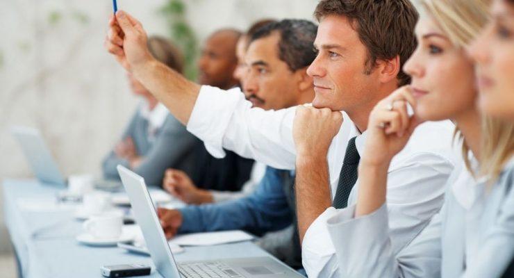 man+raising+hand+business+meeting